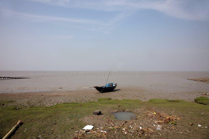 Łodzie rybacy splatali w błocie przy niskim przypływem na wybrzeżu zatoka bengalska, India zdjęcie royalty free
