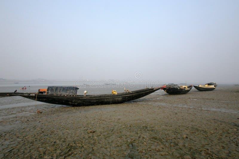 Łodzie rybacy splatali w błocie przy niskim przypływem na wybrzeżu zatoka bengalska, India zdjęcia royalty free