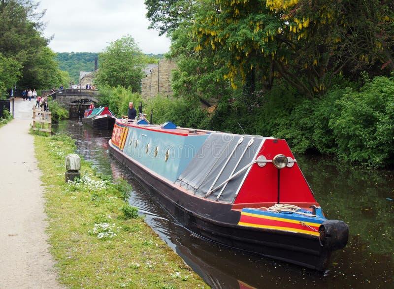 łodzie z kanału wintage przepływające przez zamek czarnej dziury w hrabstwie Hebden Bridge West Yorkshire z ludźmi obserwującymi  fotografia stock