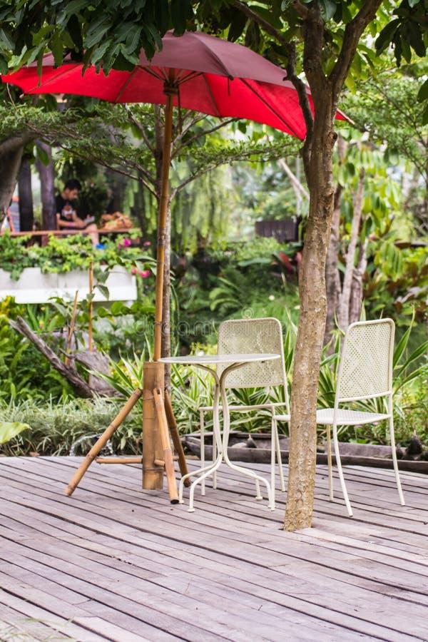 Łomotać stół z krzesłami i czerwonym parasol w ogródzie zdjęcie royalty free