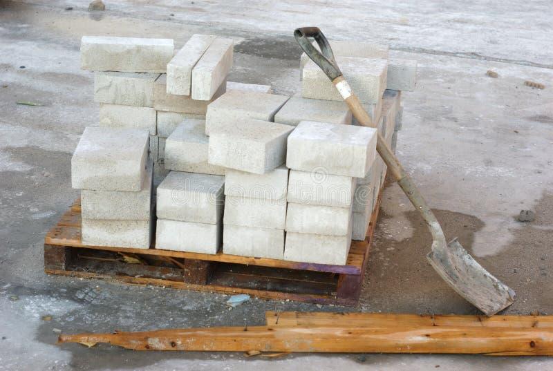 Łopata i cegły na betonowej podłoga przy budową obraz royalty free