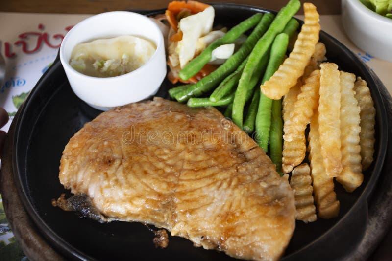 Łosoś piec na grillu, sosu kumberland z gotowaną jarzynową mieszanką i smażąca grula na gorącym stalowym niecka serw łomota w res zdjęcie royalty free