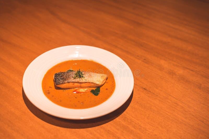 Łososiowa ryba z currym w naczyniu na stołowym gościu restauracji fotografia stock