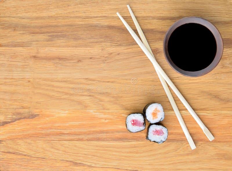 Łososiowy rollsi, chopsticks i soja kumberland na drewnianym stole, obrazy royalty free