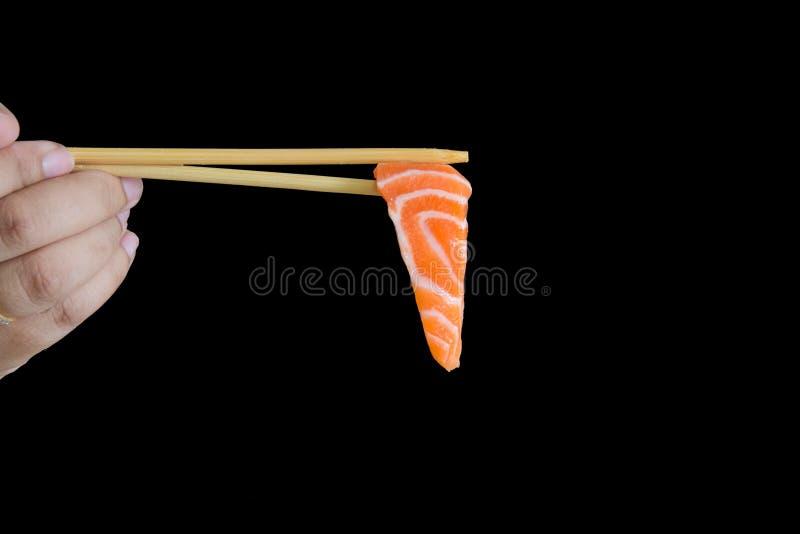 Łososiowy Sashimi na chopstick z czarnym tłem obraz stock
