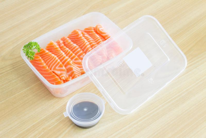 Łososiowy Sashimi wśrodku plastikowego pudełka zbiornika przygotowywającego słuzyć posiłek z soja kumberlandem w plastikowym fili zdjęcie royalty free