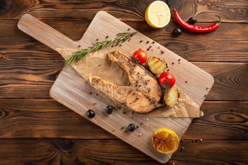 Łososiowy stek z pikantność i ziele na drewnianym tle fotografia stock