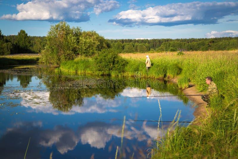 Łowić na jeziorze z lelujami w wiejskiej lokaci obrazy stock