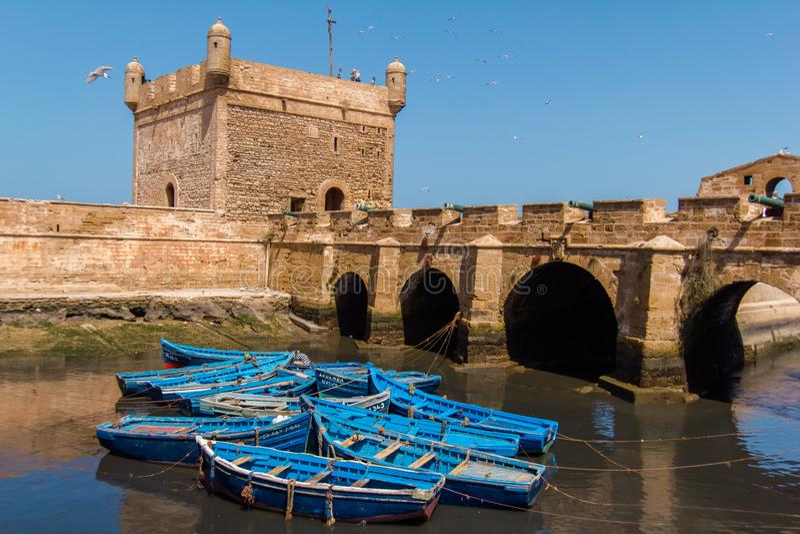 Łowić piękne błękitne łodzie, przekładnię i chwyta na tle Castelo real Mogador w Essaouira starym schronieniu, zdjęcie stock