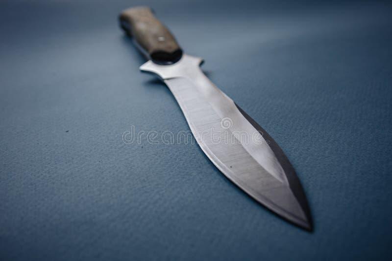 Łowiecki nóż na błękitnym monophonic tle izolujący nóż fotografia stock