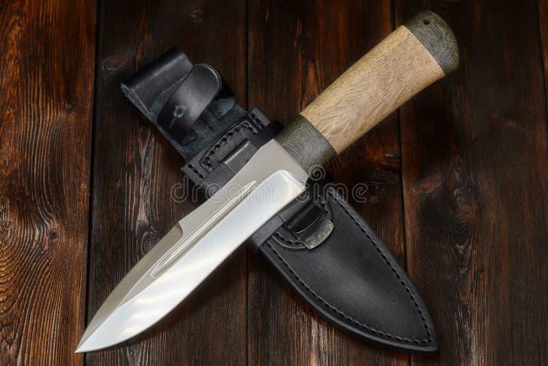 Łowiecki stalowy nożowy handmade na drewnianym tle, zakończenie zdjęcia stock