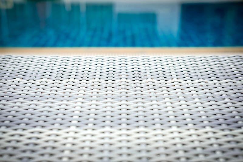 Łozinowego rattan basenu słońca łóżkowy deckchair przy basenem fotografia stock