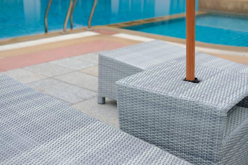 Łozinowego rattan basenu słońca łóżkowy deckchair przy basenem zdjęcia royalty free