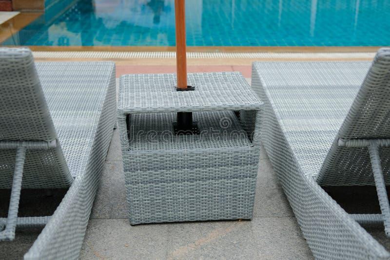 Łozinowego rattan basenu słońca łóżkowy deckchair przy basenem obraz stock