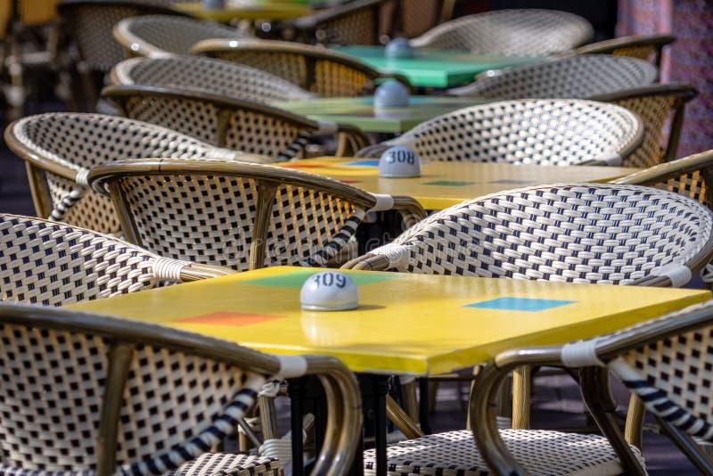 Łozinowi krzesła i kolorowi stoły w plenerowej kawiarni obrazy stock