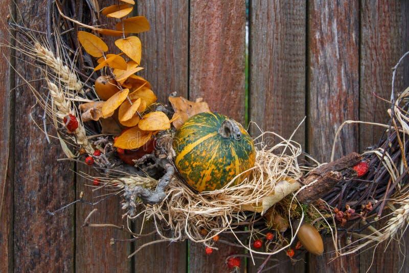 Łozinowy jesień wianek z jagodami i banią na nieociosanym drewnianym płotowym tła zbliżeniu obraz royalty free