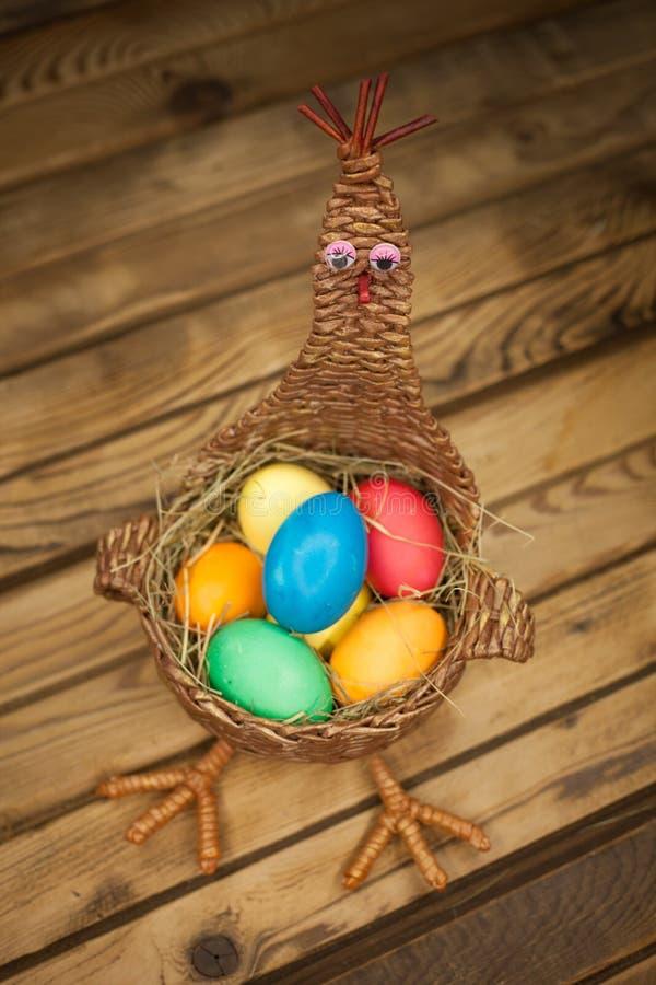 Łozinowy kosz w postaci kurczaka z barwionymi Wielkanocnymi jajkami fotografia royalty free