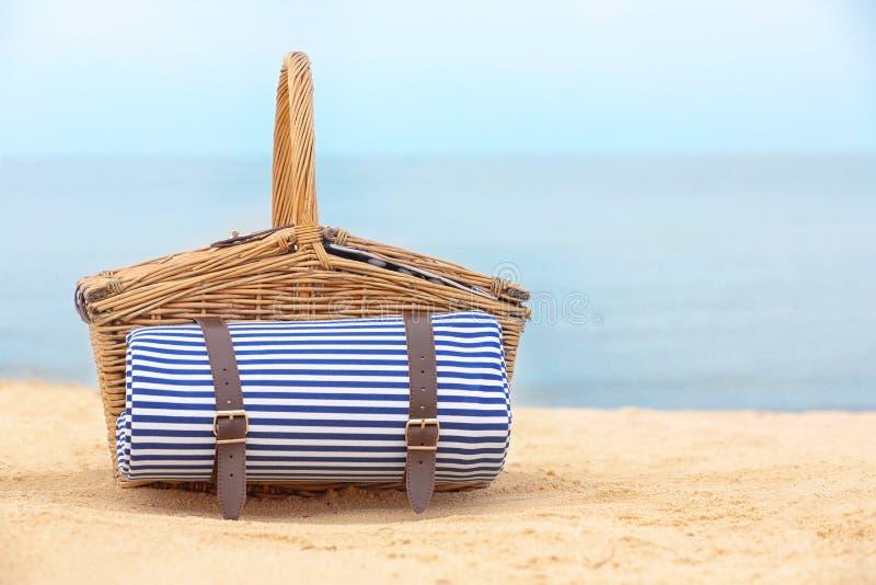Łozinowy pykniczny kosz z koc na piasku blisko morza zdjęcie royalty free