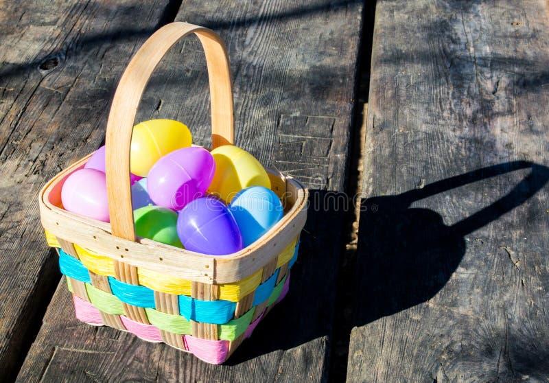 Łozinowy Wielkanocny kosz wypełniający z kolorowymi jajkami zdjęcia royalty free