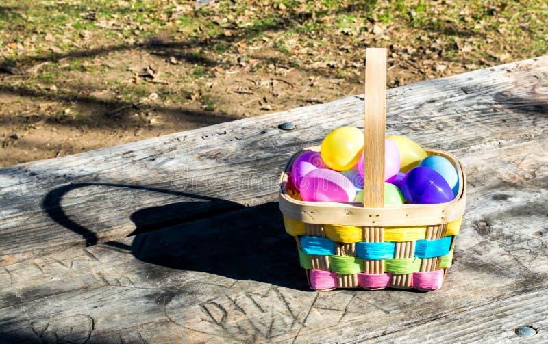 Łozinowy Wielkanocny kosz wypełniający z kolorowymi jajkami zdjęcia stock