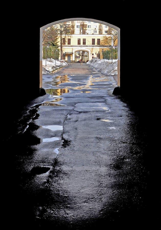 Łuk w ciemnym alleyway z mokrym asfaltem po tym jak deszcz który spada na jaskrawej ulicie obraz stock