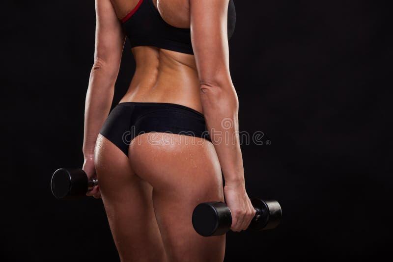 Łup atrakcyjni sportowi kobiety mienia dumbbells, tylny widok odizolowywający na ciemnym tle z copyspace obrazy royalty free