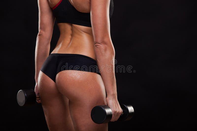 Łup atrakcyjni sportowi kobiety mienia dumbbells, tylny widok odizolowywający na ciemnym tle z copyspace fotografia royalty free