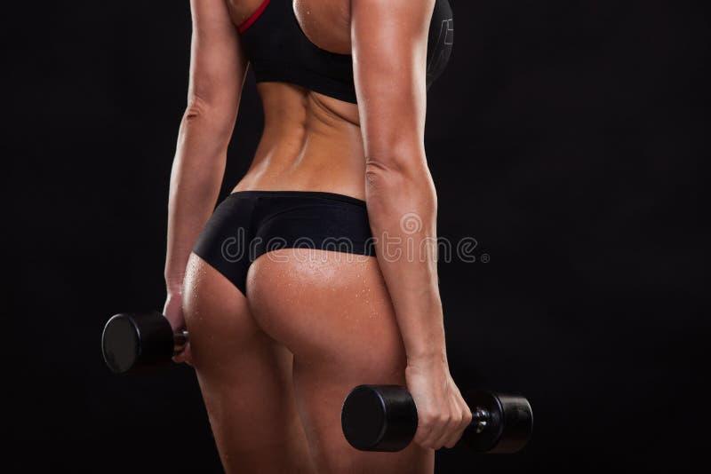 Łup atrakcyjni sportowi kobiety mienia dumbbells, tylny widok odizolowywający na ciemnym tle z copyspace zdjęcia stock