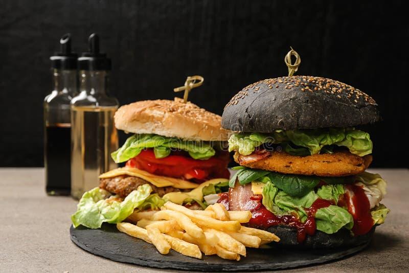 Łupkowy talerz z smakowitymi hamburgerami i francuzem smaży na stole obraz royalty free