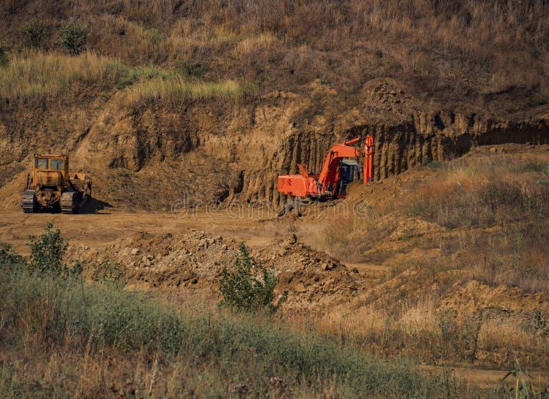 Łupu ekskawatoru ładowacza równiarki wiadra pracy środowiska glinianego rozwoju ekologii krajobrazu górniczy słoneczny dzień obrazy stock