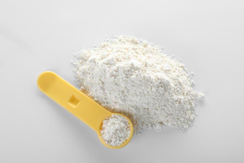 Łyżka i stos proteina proszek na białym tle zdjęcie stock