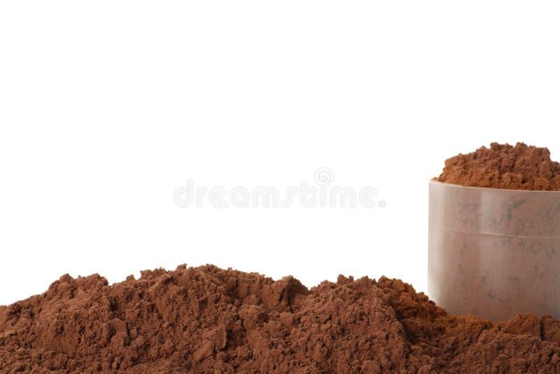 Łyżkuje i stos czekoladowy proteina proszek na bielu obraz royalty free