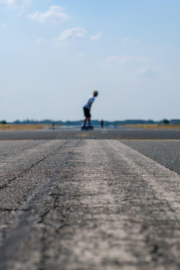 Łyżwiarka na pustej asfaltowej drodze, pasie startowym na poprzednim lotnisku/ zdjęcie royalty free