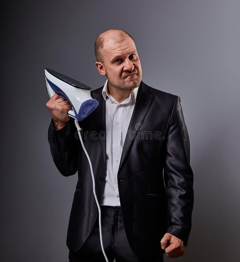 Łysej zabawy nieszczęśliwy agresywny komiczny biznesowy mężczyzna trzyma domu żelazo i chce uderzać w kostiumu na popielatym tle obrazy royalty free