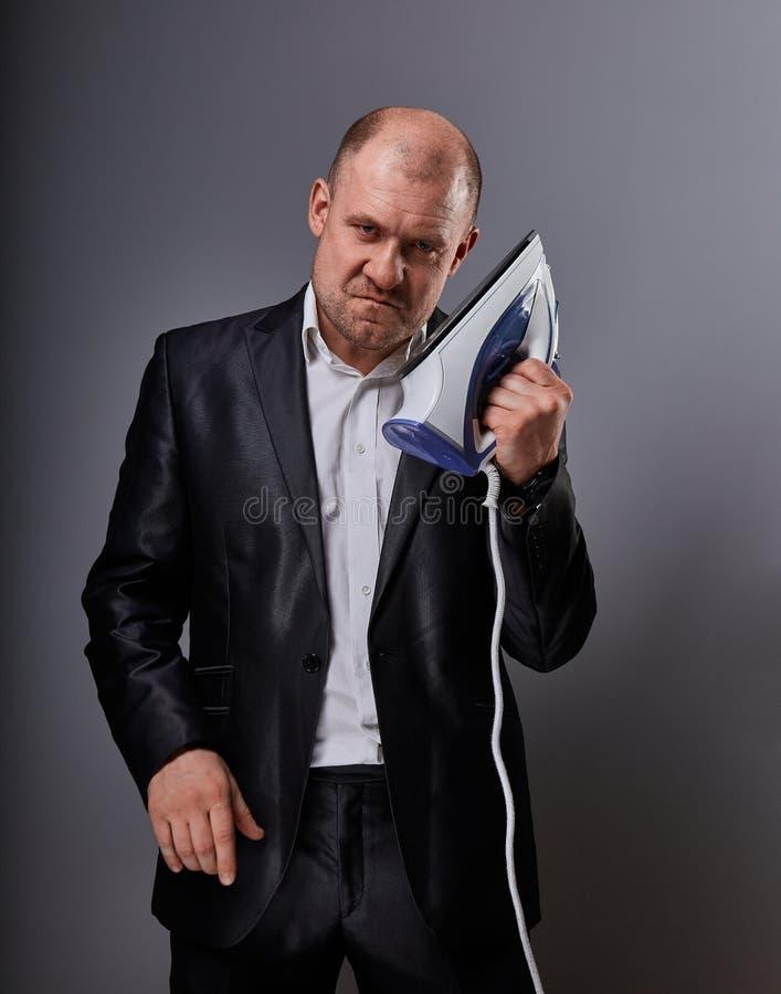 Łysej zabawy nieszczęśliwy agresywny komiczny biznesowy mężczyzna trzyma domu żelazo i chce uderzać w kostiumu na popielatym tle  obraz stock