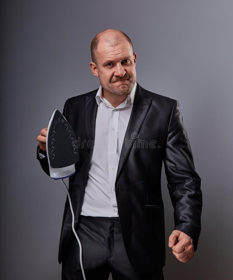 Łysej zabawy nieszczęśliwy agresywny komiczny biznesowy mężczyzna trzyma domu żelazo i chce uderzać w kostiumu na popielatym tle  obraz royalty free