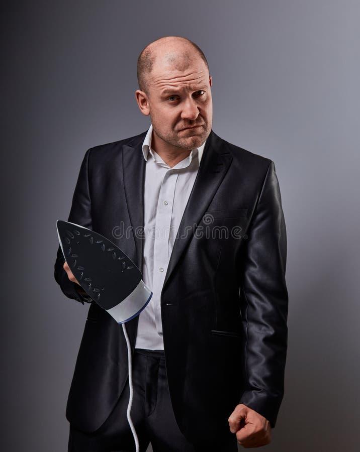 Łysej zabawy nieszczęśliwy agresywny komiczny biznesowy mężczyzna trzyma domu żelazo i chce uderzać w kostiumu na popielatym tle  fotografia stock