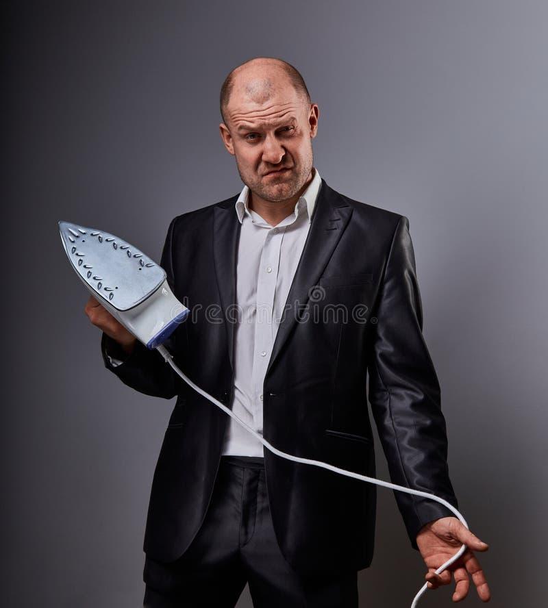 Łysej zabawy ponury agresywny komiczny biznesowy mężczyzna trzyma domu żelazo i chce uderzać w kostiumu na popielatym tle zbliżen zdjęcie stock