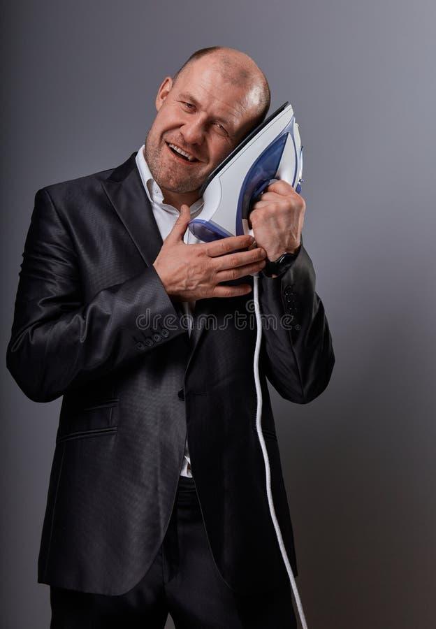 Łysej zabawy szczęśliwy komiczny biznesowy mężczyzna trzyma domu żelazo blisko twarzy z miłością w kostiumu na popielatym tle fotografia royalty free