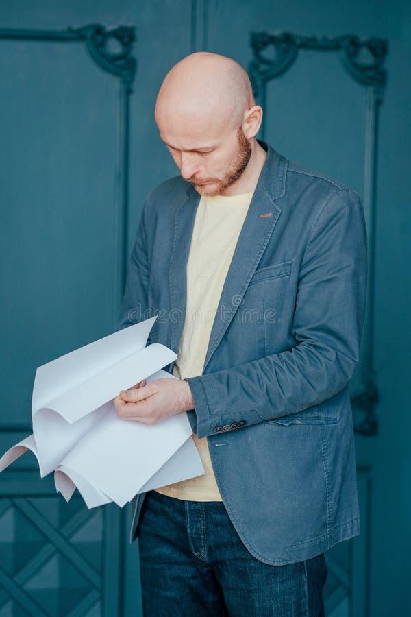 Łysy brodaty mężczyzna w niebieska marynarka kostiumu mienia prześcieradłach papier w rękach, zakończenie w górę zdjęcie stock