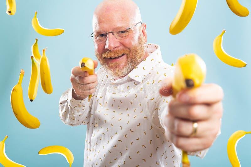 Łysy człowiek otoczony bananami obraz royalty free