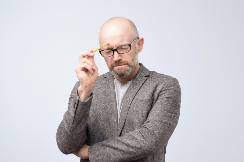 Łysy dojrzały europejski mężczyzna myśleć o coś z ołówkiem Dlaczego rozwiązywać ten problem obrazy royalty free