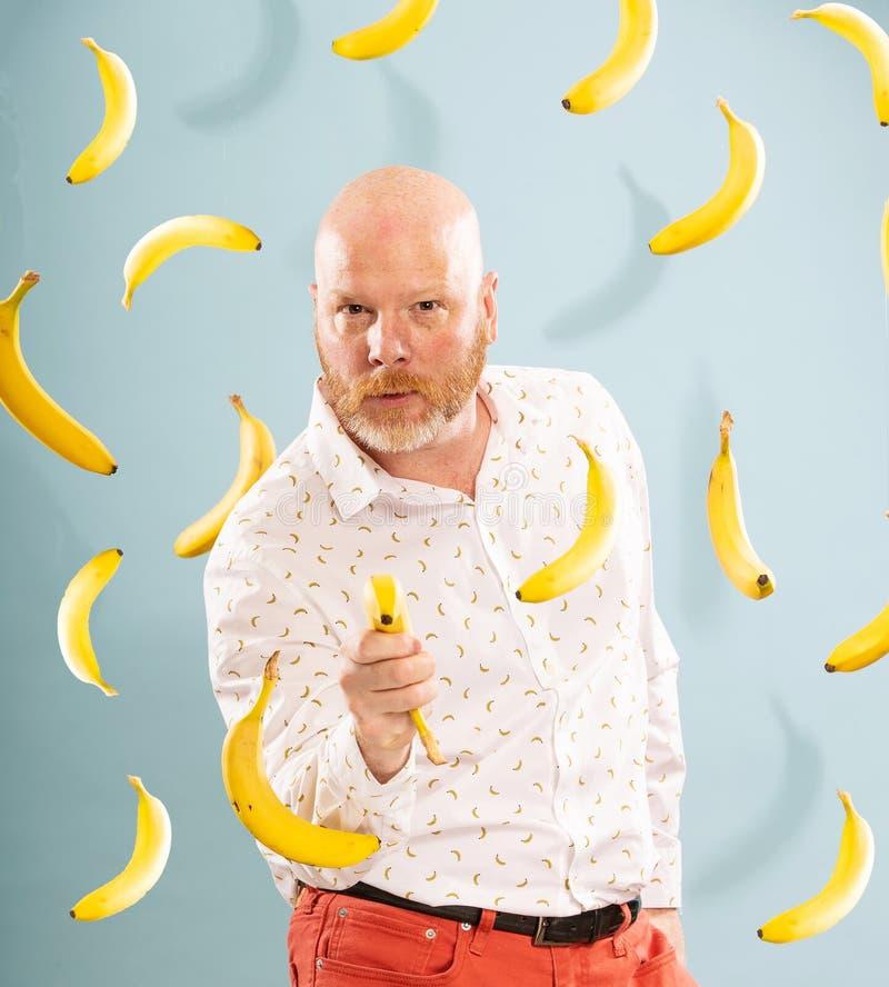 Łysy mężczyzna otoczony bananami wskazującymi sztuczny bananowy pistolet zdjęcia royalty free
