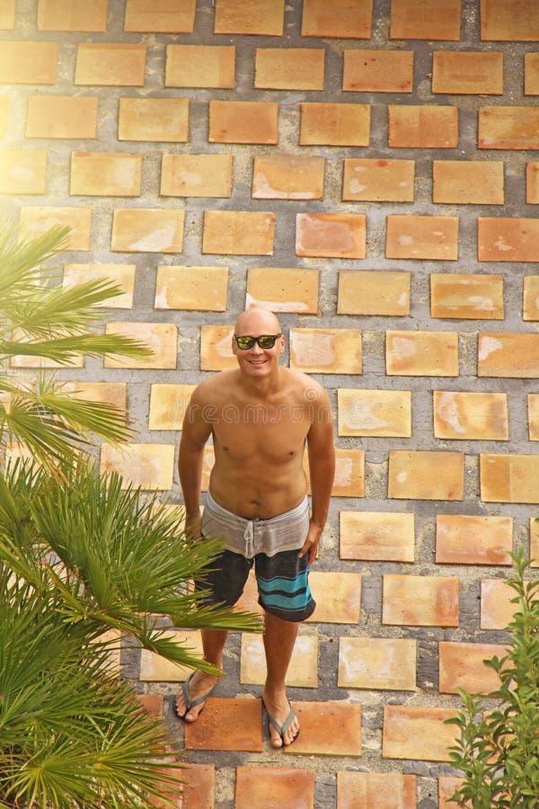 Łysy mężczyzna z nagą półpostacią w skrótach, przeciw tłu o zdjęcie stock