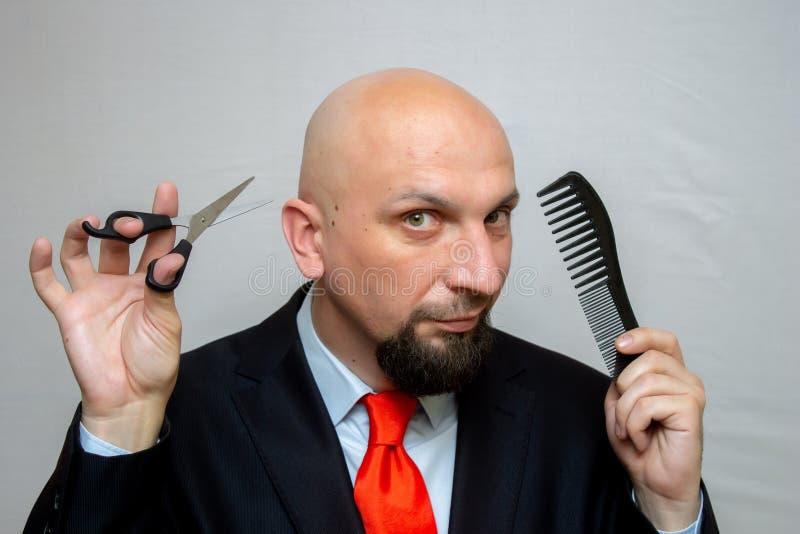 Łysy mężczyzna z nożycami i gręplą w jego rękach, ostrzyżenie w fryzjera męskiego sklepie zdjęcia royalty free