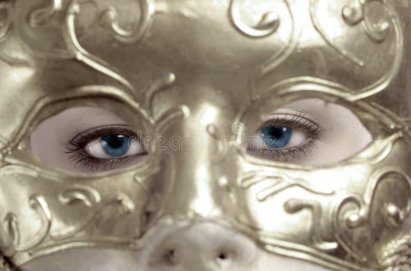œil bleu derrière le masque images stock