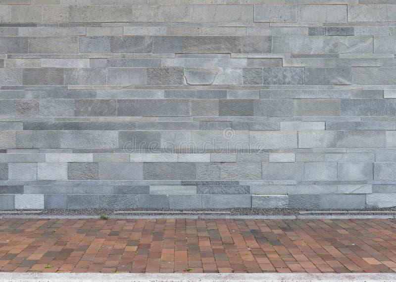 Ściana granitów kamienie z brukującą podłoga jako tło zdjęcia royalty free