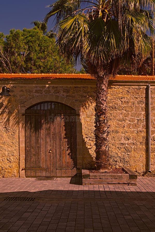 Ściana z bramą i drzewkiem palmowym fotografia stock