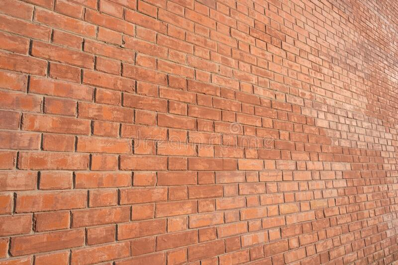 Ściana z cegły, widok kątowy, oświetlona ciepłym światłem obraz royalty free