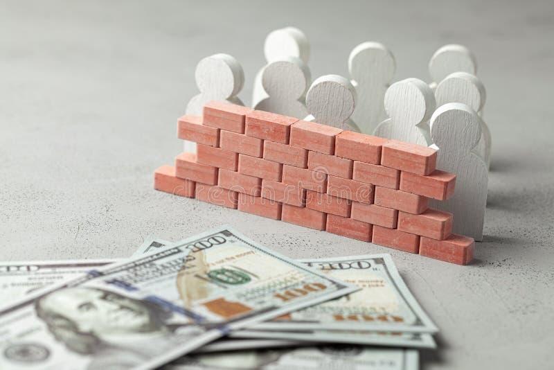 Ściana z cegieł oddziela pieniądze od ludzi Ściana z jednej strony wiele biznesmeni z stertą pieniądze obrazy stock